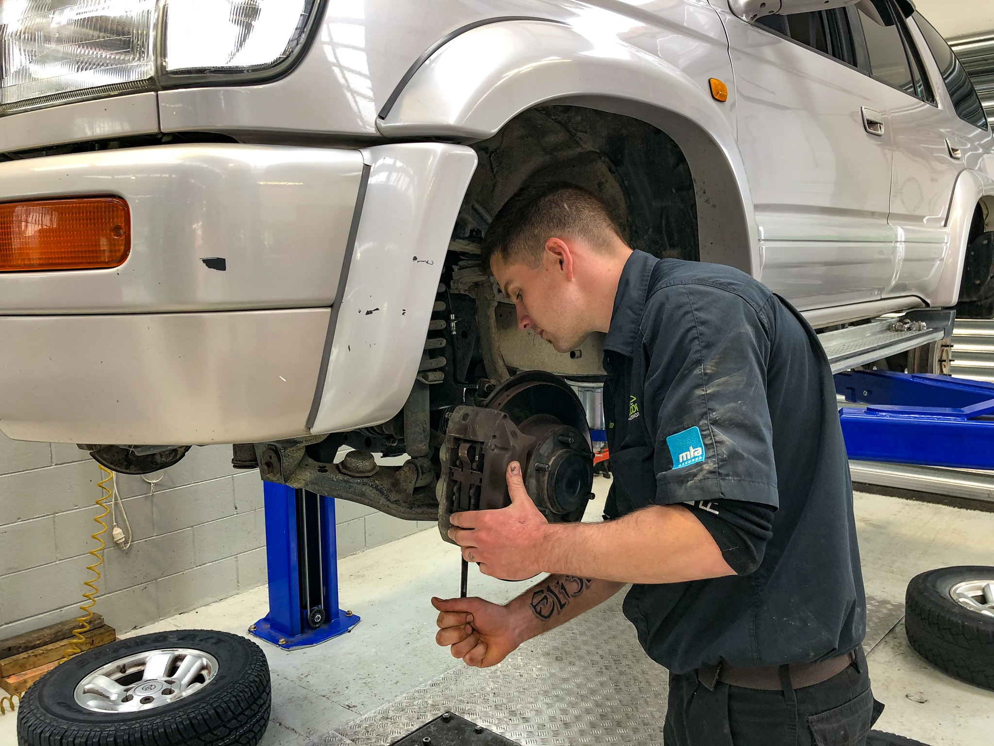 One of our experienced mechanics doing a brake repair on a vehicle in Woodend